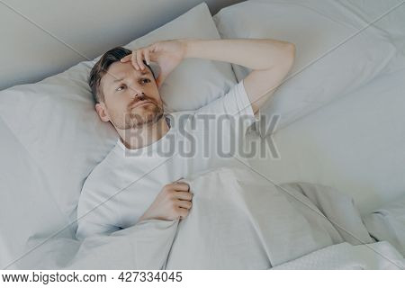 Young Upset And Tired Bearded Man Lying On Bed With Open Eyes And Cannot Sleep, Male Having Insomnia
