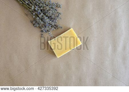 Piece Of Natural Lavender Soap And Bouquet Of Dried Lavender On Craft Paper. Top View, Flat Lay. Cop