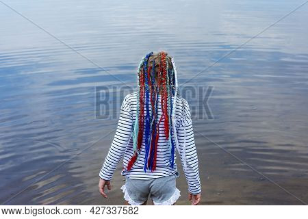 A Teenage Girl With Bright Multicolored Ribbons Braided In Pigtails, A Modern Youth Hairstyle, A Gir
