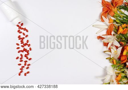 Orange Capsules Of Lutein And Medicinal Plants On A White Background With Place For Text. Supplement