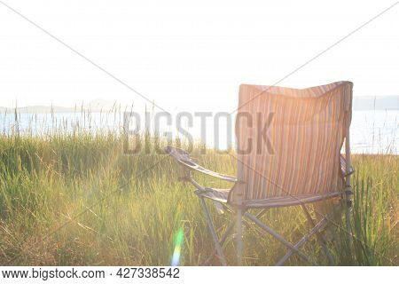 An Empty Tourist Chair In Warm Sun Rays By The River. Dreamy Summer Vacation And Relaxing On The Gra