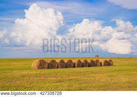 Summer Landscape With Row Of Hay Bales On Farmland Against Awesome Cloudy Sky.