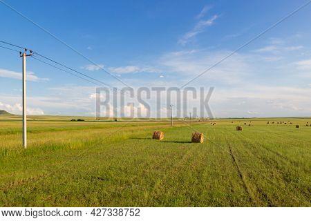 Summer Landscape With Straw Bales On Farmland.