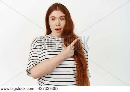 Portrait Of Surprised Cute Girl With Red Hair, Raising Eyebrows And Gasp Wow, Pointing At Upper Righ