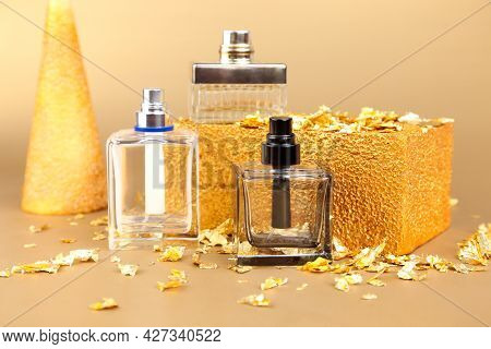 Three Unbranded Perfume Spray Bottles, Pieces Of Gold Paper And Golden Rectangular Shape On Golden B