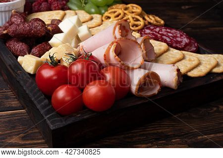 Close-up Of Charcuterie Board With Sausage, Fruit, Crackers And Cheese On A Dark Wooden Background.