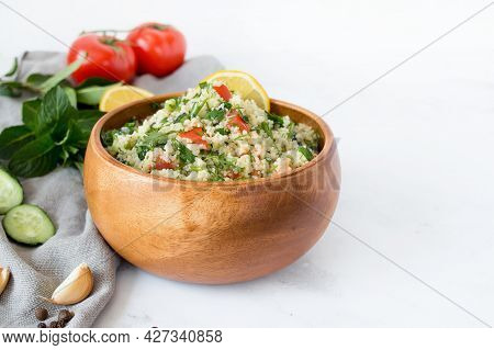 Traditional Oriental Salad Tabouleh With Couscous Or Bulgur On A White Marble Background.