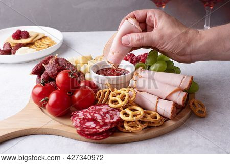 Female Hand Dipping A Slice Of Ham In Sauce On Round Charcuterie Board With Sausage, Cheese, Cracker