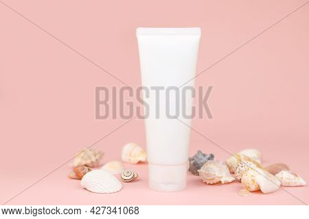 Unbranded White Squeeze Bottle Cream Tube And Seashells A Lot On Pink Background. Cosmetics With Cal