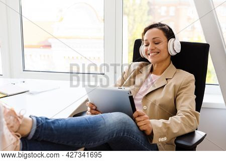 Middle eastern woman in headphones using tablet computer while sitting at office
