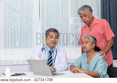 Asian Man Doctor Is Using Computer To Explain The Symptoms And Treatment Procedures Let The Elderly