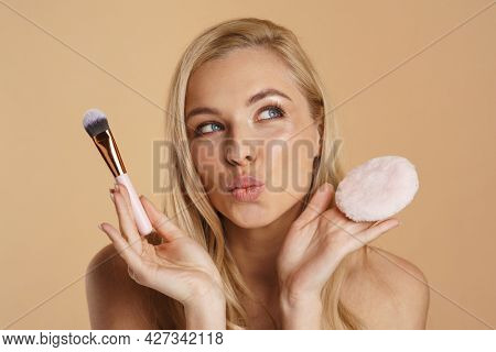 Smiling young blonde woman with long hair with bare shoulders standing over beige background, holding powder puff and makeup brush