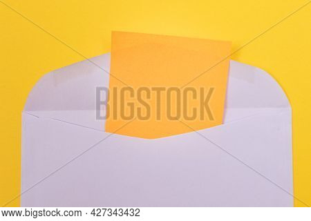 Violet Envelope With Blank Orange Sheet Of Paper Inside, Lying On Yellow Background - Mock Up With C