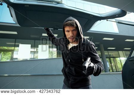 Aggressive european robber looking in car trunk. View from auto trunk with human victim. Male bearded bandit wear black hoodie with gloves and hold pistol. Concept of kidnapping. City daytime