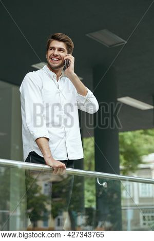 Pleased european businessman talking on mobile phone and looking somewhere. Young man standing on balcony of modern office building in city. Smiling bearded guy wear white shirt and jeans. Daytime