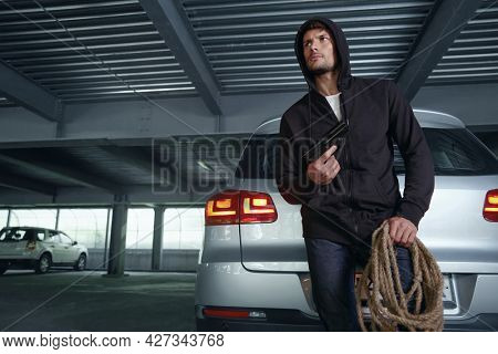 Concentrated european robber standing near private automobile. Bottom view of male bearded bandit wear black hoodie and hold pistol with rope. Concept of robbery and kidnapping. Inside parking lot