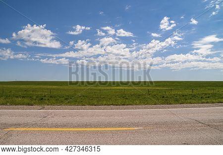 Badlands National Park, Sd, Usa - June 1, 2008: Intense Green Flat Prairie Under Blue Cloudscape At
