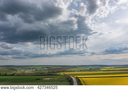 Aerial shot, overcast clouds above yellow agricultural field of rape, copyspace