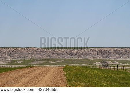 Badlands National Park, Sd, Usa - June 1, 2008: Landscape With Beige Geologic Deposits Appearing Fro