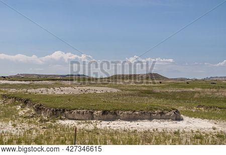 Badlands National Park, Sd, Usa - June 1, 2008: Green Prairie Expanse With Geologic Deposits Under B