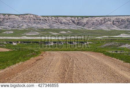 Badlands National Park, Sd, Usa - June 1, 2008: Brown Gravel And Dirt Road Descends Onto Green Prair