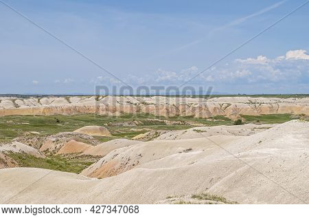 Badlands National Park, Sd, Usa - June 1, 2008: Wide Landscape With Only Few Green Patches Among Bei