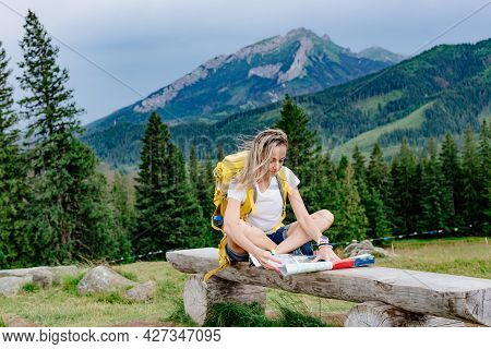 Female Tourist With Backpack Sits On A Bench With A Paper Map In Mountain.