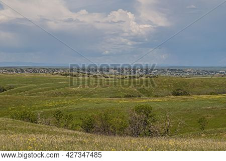Badlands National Park, Sd, Usa - June 1, 2008: Wide Green Landscape With Prairie Hills And Geologic
