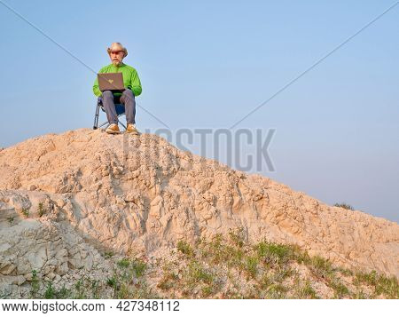Senior man in cowboy hat is sitting on a folding chair and working on laptop in the middle of nowhere, early morning in the badlands of Pawnee National Grassland in Colorado