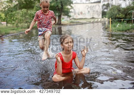 Cute Girl Sitting In Lotus Pose In Puddle After Warm Summer Rain And Her Brother Jumping And Swimmin