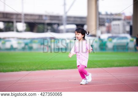 Active Asian Girl Running On Red Stadium. In Summer Or Spring Time. Child Exercise Jogging In The Ev