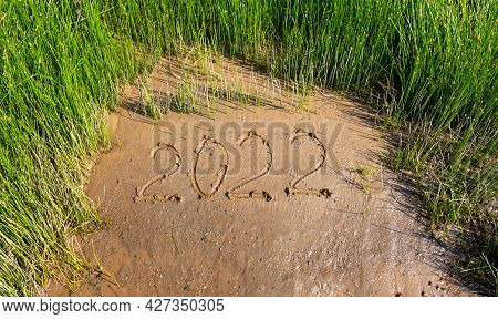 In The Middle Of The Green Grass, The Numbers 2022 Are On The Wet Sand. The Concept Of The New Year