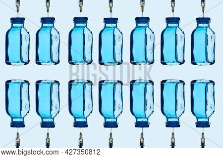 some vaccine bottles, with a blue liquid inside, and some syringes stuck on them, arranged in different lines on a pale blue background
