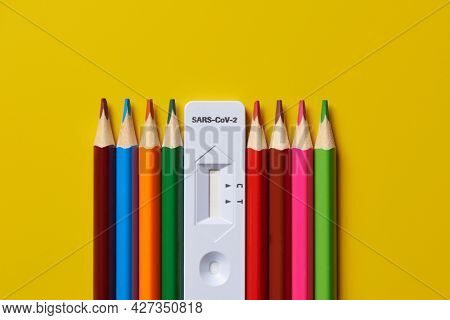 high angle view of covid-19 antigen diagnostic test device and pencils of different colors, on a yellow background