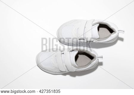 Flat Lay White Childrens Running Shoes Imitating Walking With Hard Shadows Isolated On A White Backg