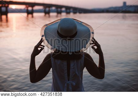 The Silhouette Of A Woman By The River At Sunset. Rear View Of The Silhouette Of A Woman In A Straw