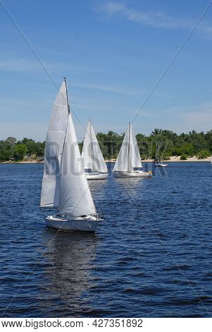 Beautiful Racing Luxury Yachts In The Sea On Blue Sky And Forest Score Background. Sailing. Yachting