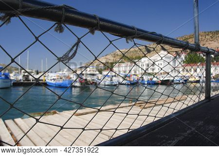 In The Foreground There Is A Long Fishing Net With Large Meshes. Through It Is Visible The Blurred L