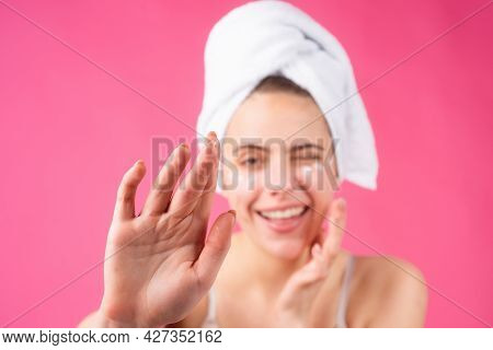 Woman With A Facial Mask. Charming Pretty Model After Bath Wrapped In Towel Applying Using Face Mask