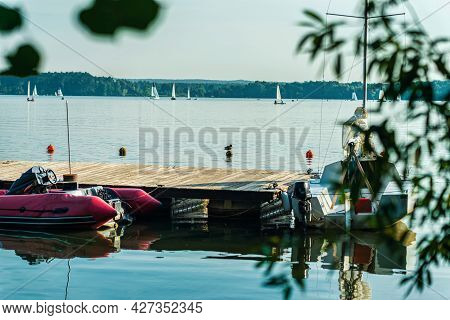 Summer Day On The Lake, River, White Sport Sailing Yachts. Inflatable Motor Boat Near The Pie