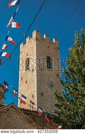 View Of Stone Steeple Tower Next To Church And Flags In Vence, A Stunning Medieval Hamlet Completely