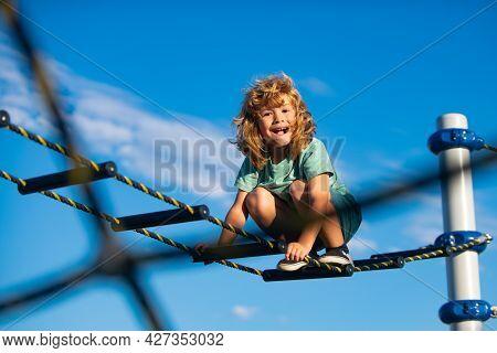 Joyful Kid Boy Having Fun On Playground Outdoors. Cute Boy Climbs Up The Ladder On The Playground. C