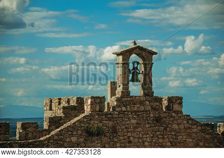 Bell On Top Of Thick Stone Wall With Crenels And Merlons At The Castle Of Trujillo. A Small Medieval