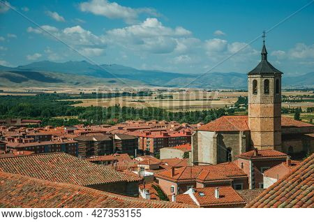 Church Bell Tower Amid Rooftops And Countryside Landscape In Avila. A Cute City With Medieval Buildi