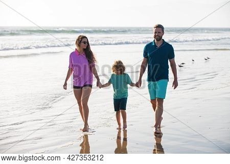 Young Family Father, Mother With Baby Son Hold Hands And Walk On Sand Beach. Active Parents And Peop