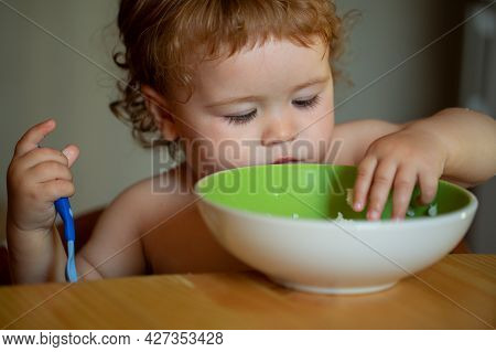 Portrait Of Cute Caucasian Child Kid With Spoon. Hungry Messy Baby With Plate After Eating Puree.