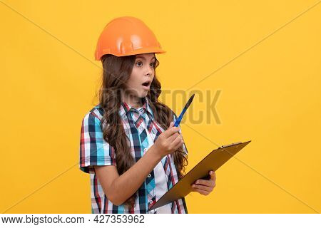 Safety Work Expertise. Amazed Girl In Protective Hard Hat Making Notes.