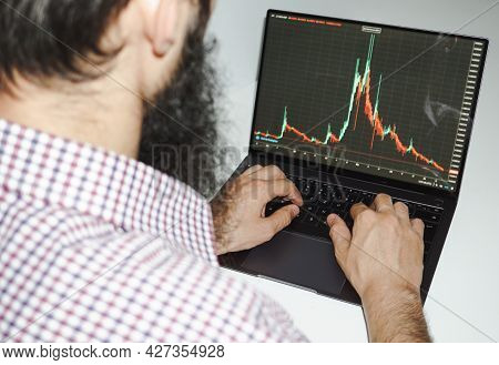 Young Man Working On Laptop With Statistics Shown About Crypto Currency - Young Bearded Man Checking