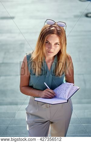 Strict Young Woman With Sketchpad Writes Something Outdoors Using Pen.