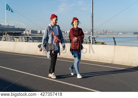 Stylish Romantic Couple Or Friends Walking Outdoors Talking. Trendy Young Hipsters With Skateboard O